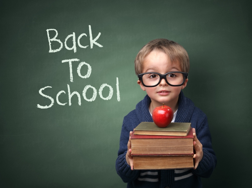 Young child holding stack of books and back to school written on