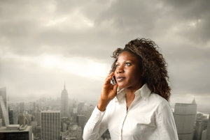 A black woman is listening at a mobile phone on a city backgroun
